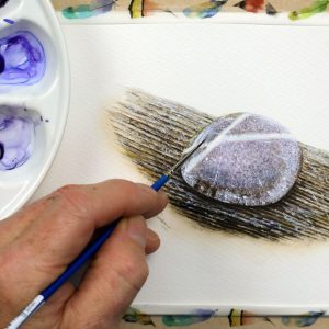 Paul Hopkinson painting a round stone in watercolour